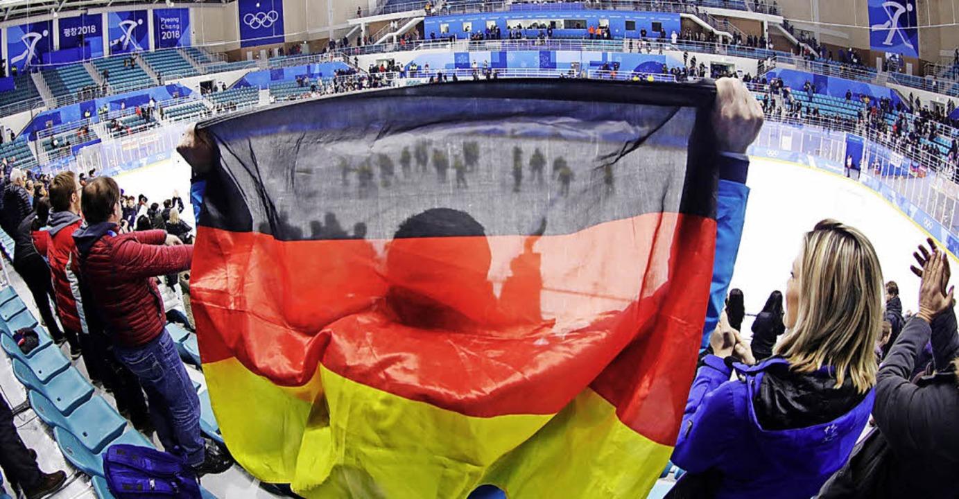 Ein deutscher Eishockey-Fan mit und ei... Können sie auch gegen Kanada jubeln?     Foto: dpa