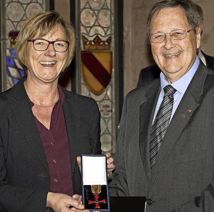 Ministerin Edith Sitzmann  überreicht Erich Birkle das Verdienstkreuz.   | Foto: Ingo Schneider