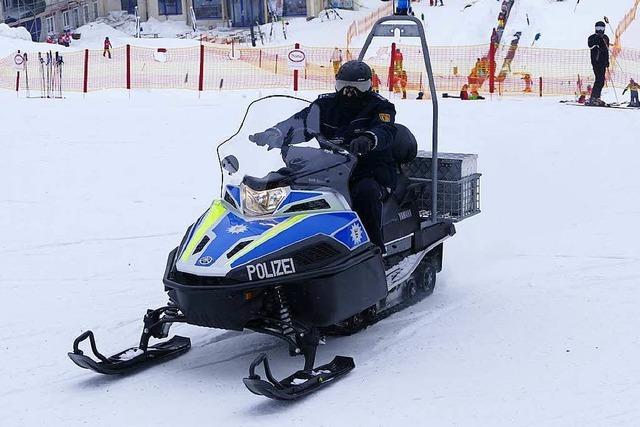 Polizisten sind am Feldberg mit dem Motorschlitten unterwegs