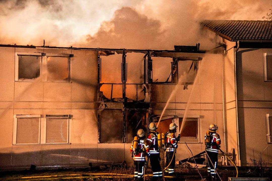 Einsatzkräfte der Feuerwehr löschen de...inem Asylbewerberheim in Kornwestheim.  | Foto: dpa