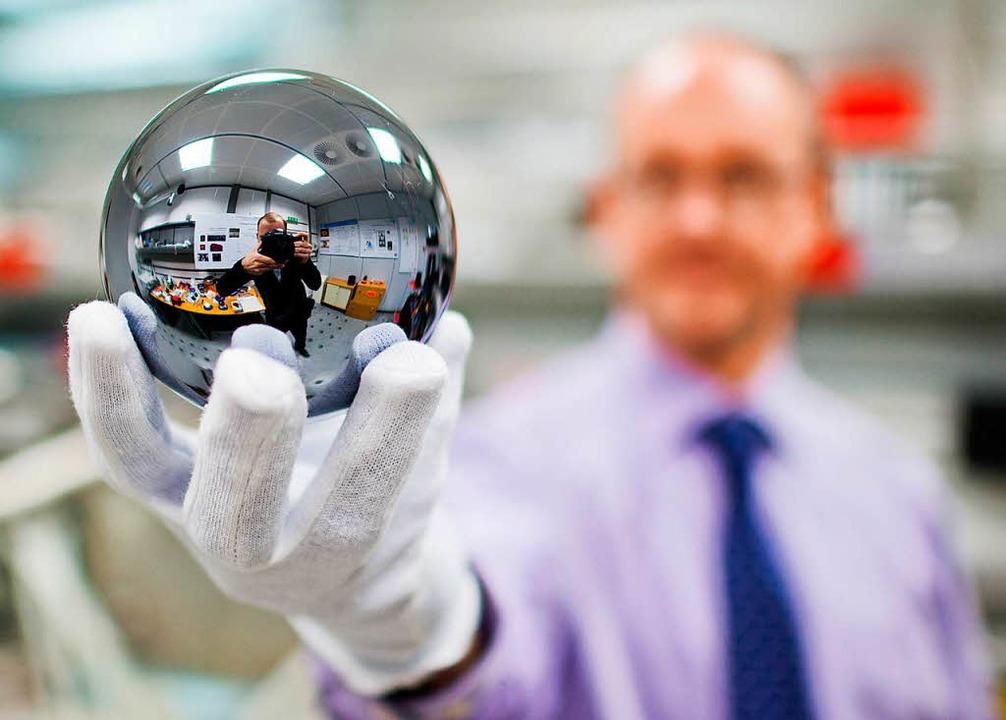 Exakt ein Kilogramm, bestehend aus rei...hält eine der neuen Kilo-Kugeln hoch.   | Foto: dpa