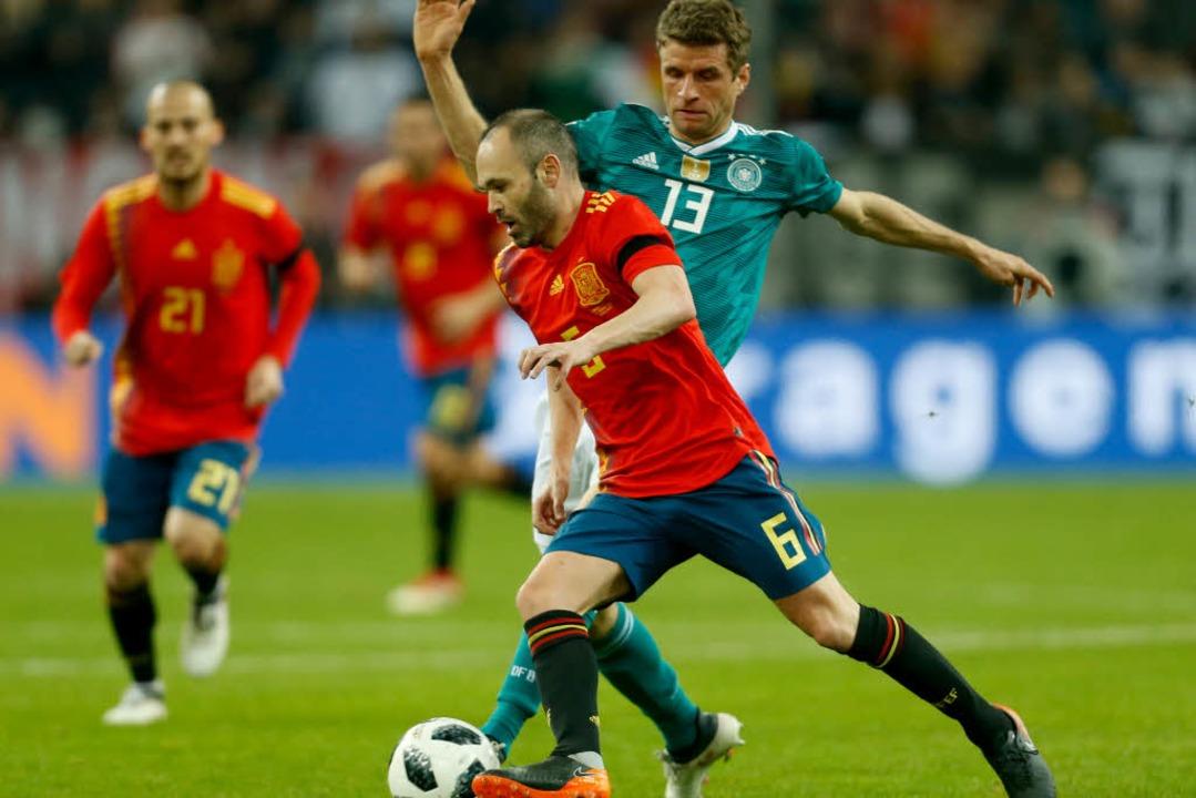 Andres Iniesta (l) und Thomas Müller von Deutschland kämpfen um den Ball.  | Foto: dpa