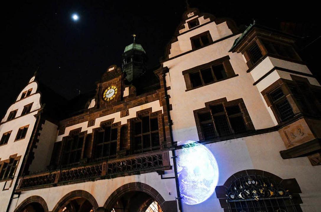 Eine Weltkugel wird bei der Klimaschut...uchtete Freiburger Rathaus projiziert.  | Foto: dpa