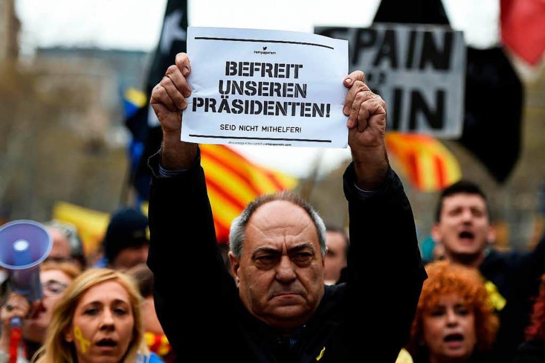 Ein Demonstrant hält in Barcelona ein  Plakat in deutscher Sprache hoch.  | Foto: AFP