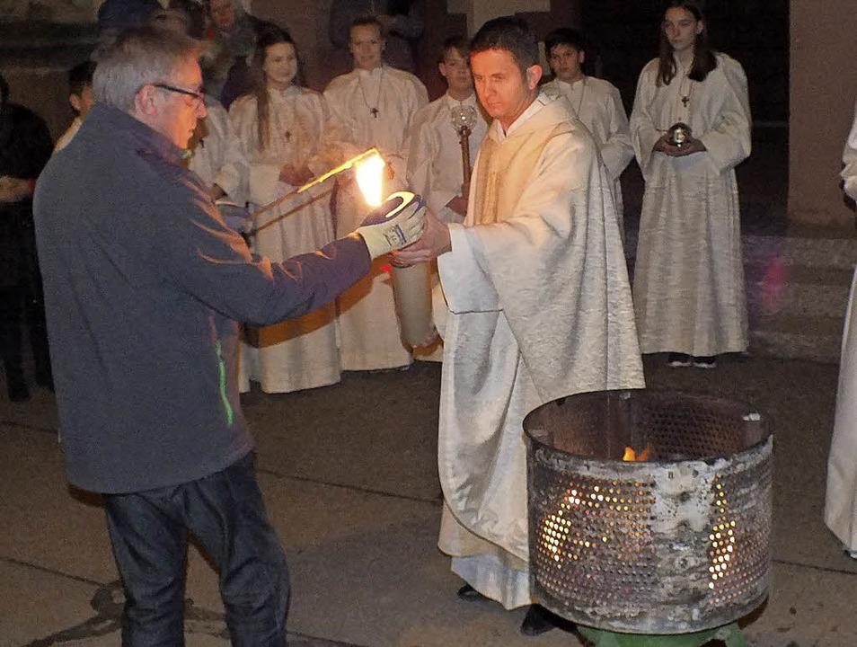 Pfarrer Michael Gartner entzündet am O...Osterkerzen der Seelsorgeeinheit Rust.    Foto: Rudi Rest
