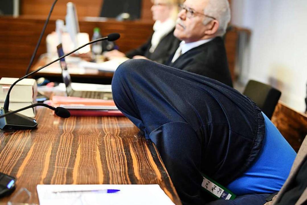 Der Angeklagte  mit einer Jacke über d...l neben seinem Verteidiger Klaus Malek  | Foto: dpa