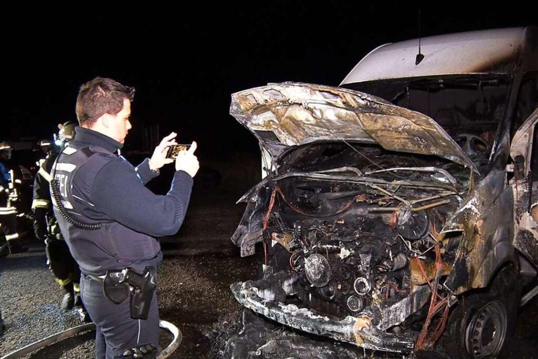 Ein Polizist fotografiert den ausgebrannten Mercedes Sprinter in Allmannsweier.  | Foto: Wolfgang Künstle