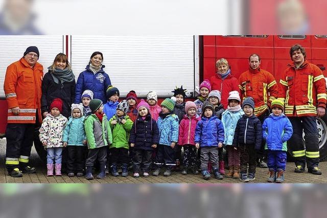 Kinder lernen etwas bei der Feuerwehr