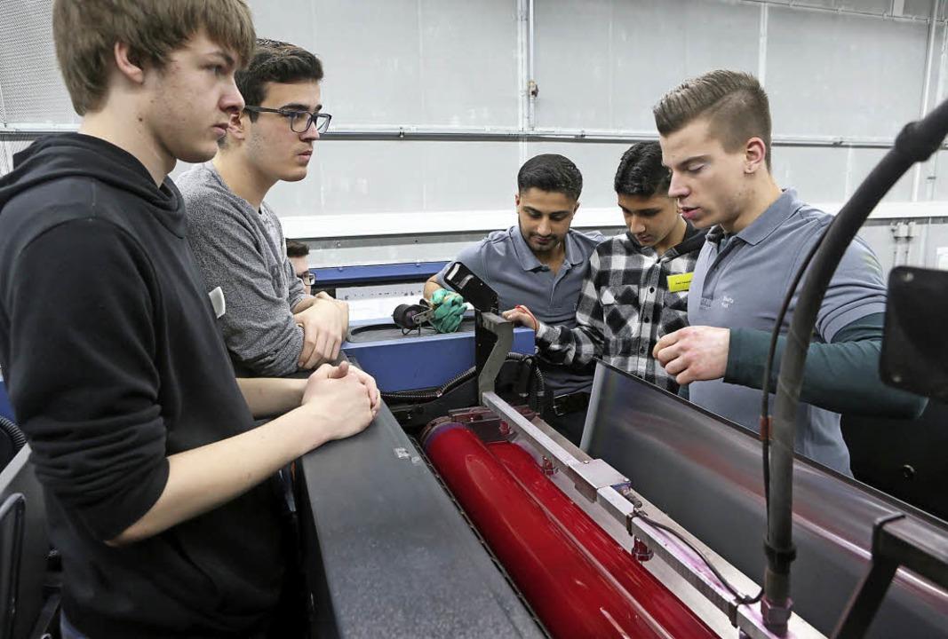 Azubis im Druckhaus Kaufmann erklären Schülern die Druckmaschine.   | Foto: Christoph Breithaupt
