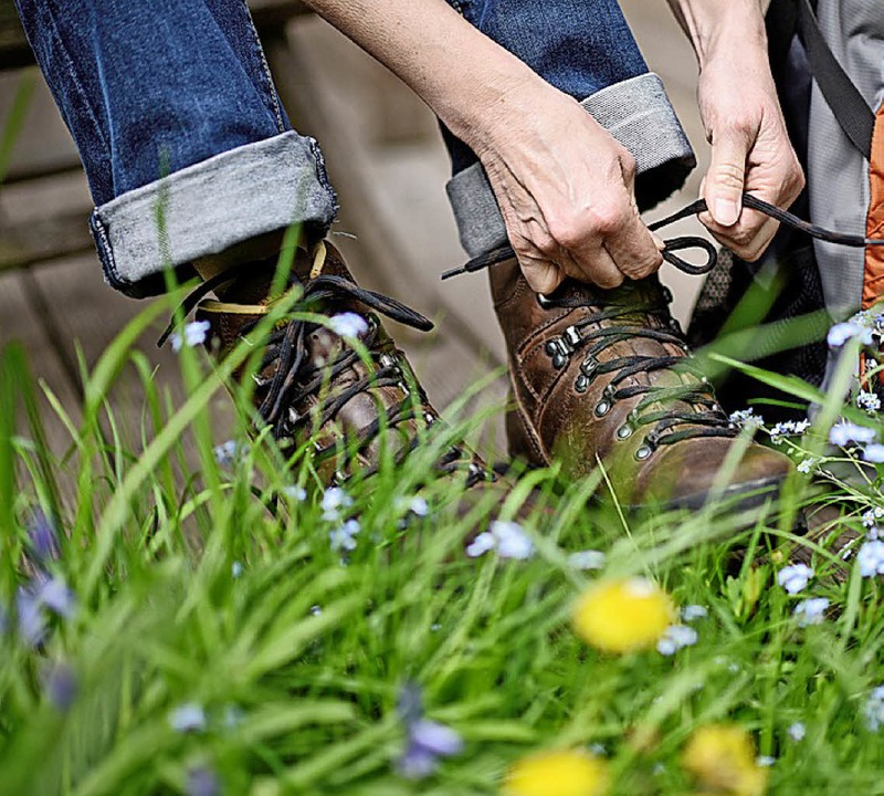 Ein Wanderer schnürt seine Schuhe.     Foto: dpa