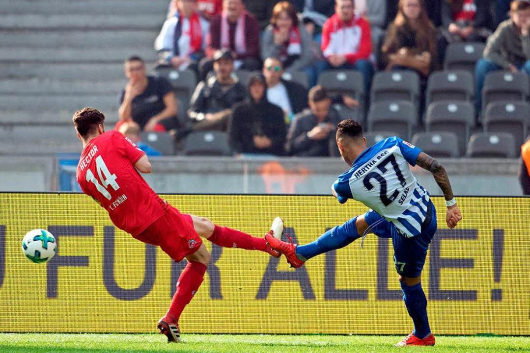 Herthas Davie Selke (r) schiesst zum 1:1 gegen Kölns Jonas Hector.  | Foto: dpa