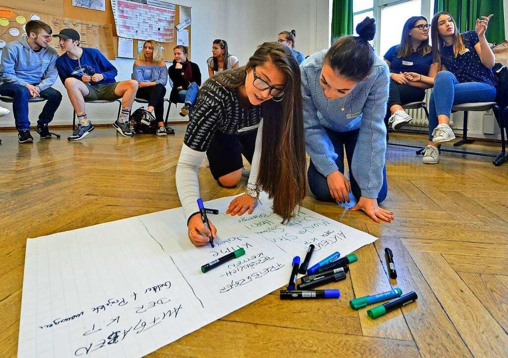 Schülerinnen  notieren, was sie über die  OB-Wahl wissen.  | Foto: Michael Bamberger