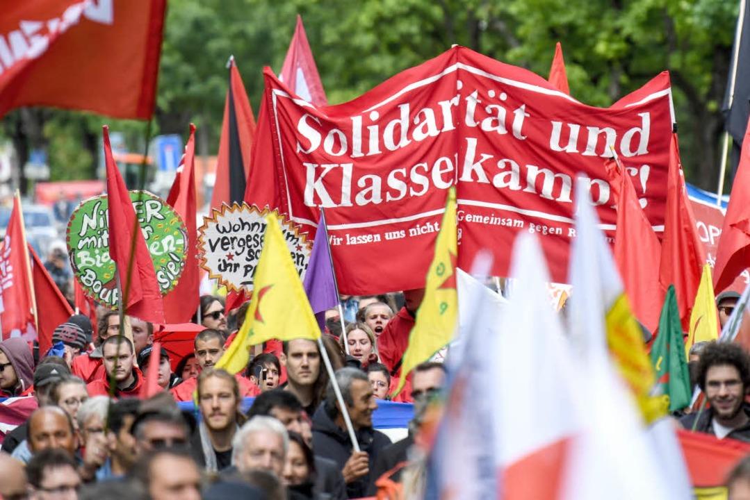 Teilnehmer ziehen beim Demonstrationszug am Tag der Arbeit durch die Innenstadt.  | Foto: dpa