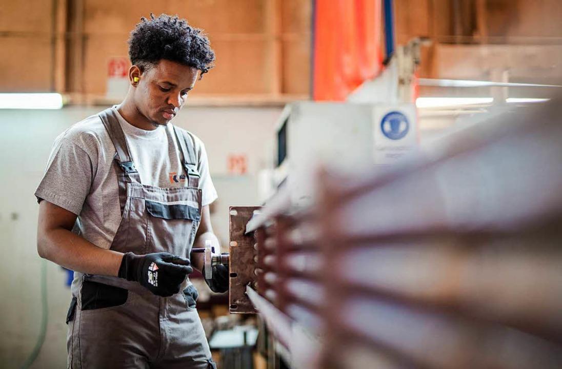 Ein Flüchtling aus Somalia arbeitet an einem Wärmetauscher in Baden-Württemberg.  | Foto: dpa