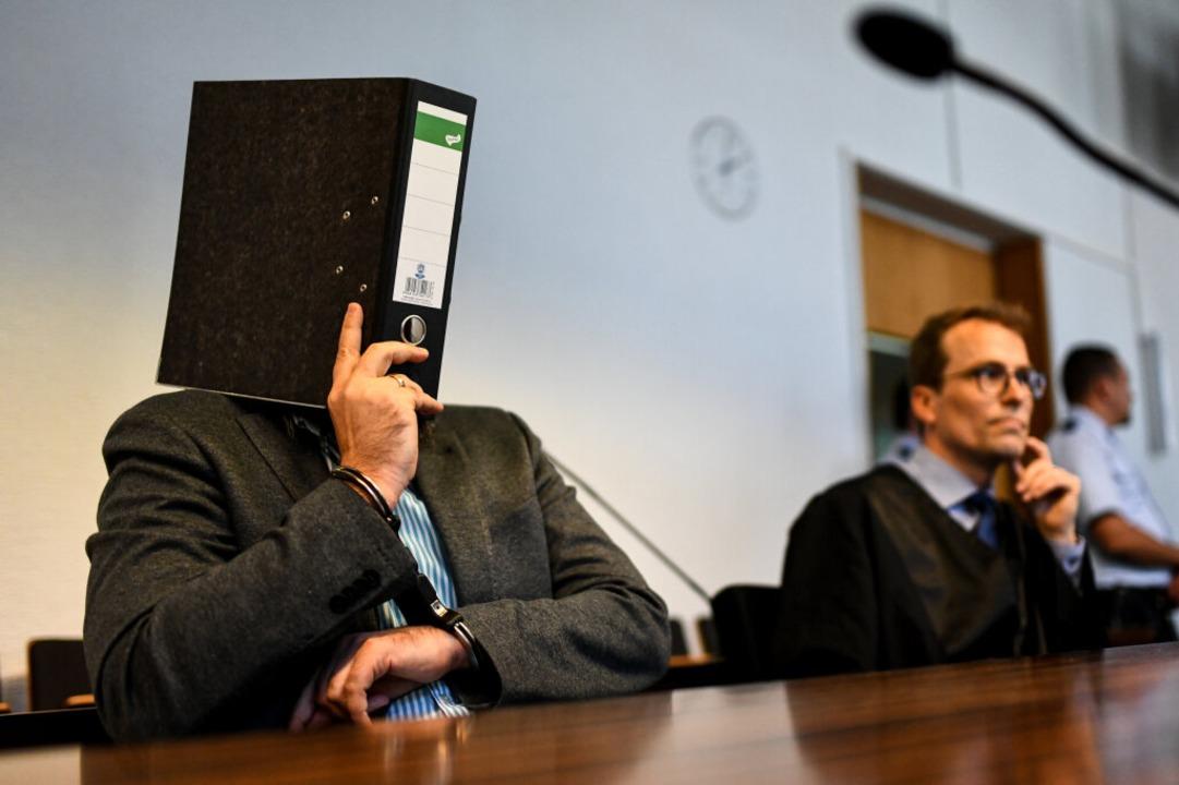 Knut S. verdeckt vor Prozessbeginn am ...r. Neben ihm sein Anwalt Holger Meier.  | Foto: dpa