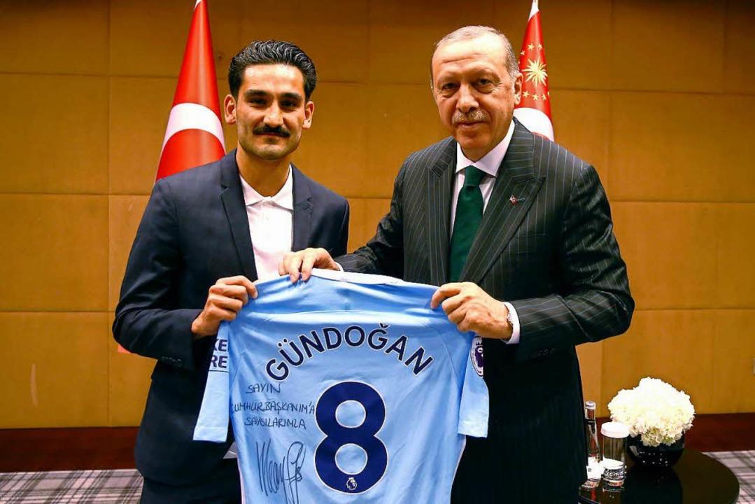 Recep Tayyip Erdogan, Staatspräsident ...ein Trikot von Gündogan in den Händen.  | Foto: dpa
