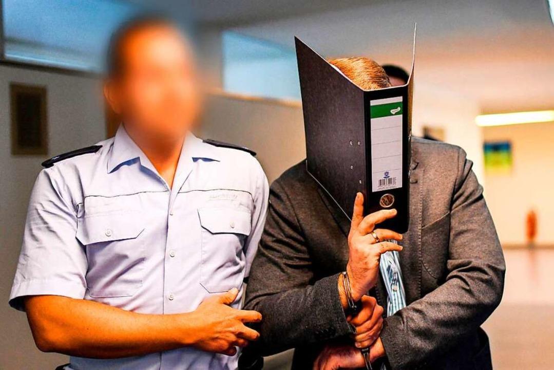 Knut S. wird am ersten Prozesstag in d...ordner vor den Kameras der Fotografen.  | Foto: dpa