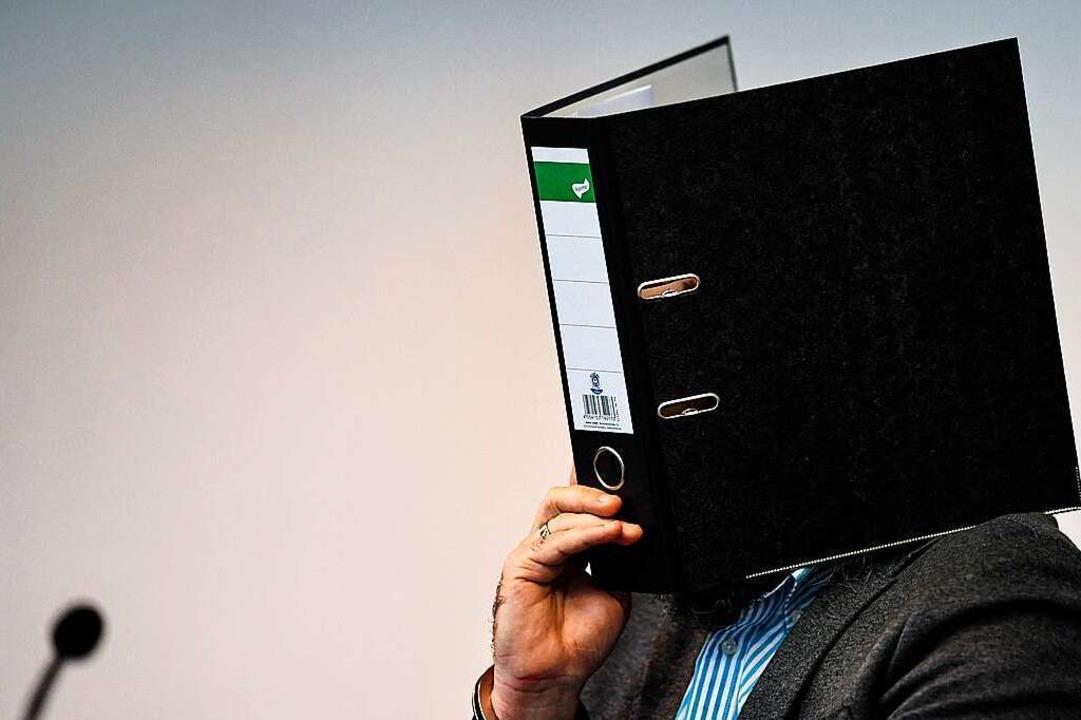 Knut S. verdeckt sein Gesicht im Freiburger Landgericht mit einem Aktenordner.  | Foto: dpa