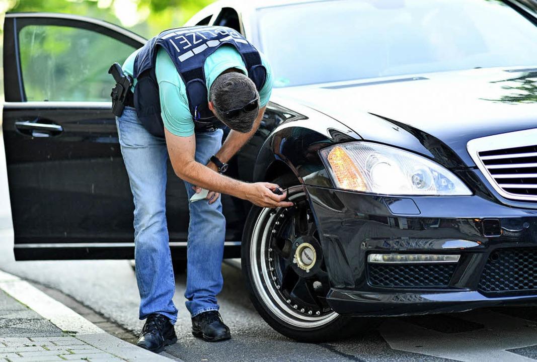Auf der Suche nach Auto-Posern kontrolliert ein Polizist ein Fahrzeug.   | Foto: DPA