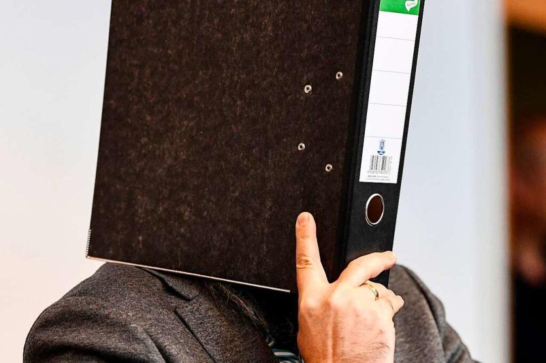 Vor der Verhandlung verbarg der Angekl...sein Gesicht hinter einem Aktenordner.  | Foto: dpa