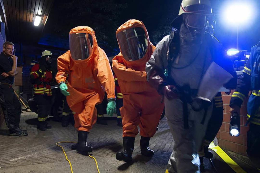 Das Gefahrgut-Team in Chemikalienschutzanzügen auf dem Weg zum Einsatzort.  | Foto: Volker Münch