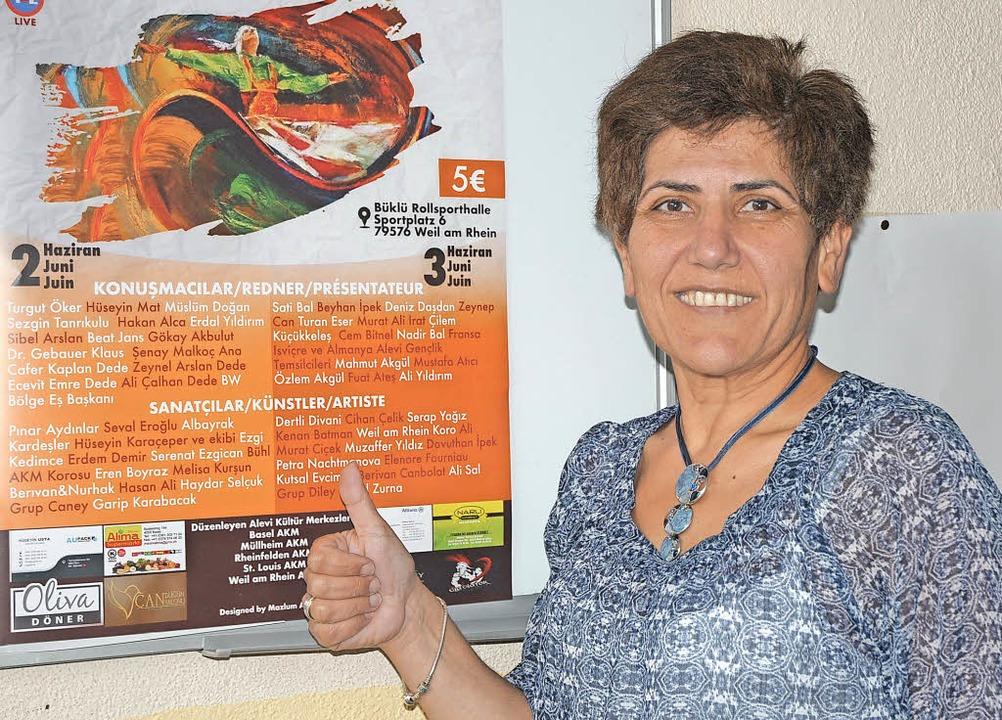 Saadet Grandazzo vor dem Plakat für das erste trinationale alevitische Festival   | Foto: Regine Ounas-Kräusel