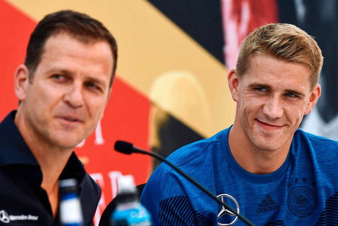 Oliver Bierhoff (links) und SC-Spieler Nils Petersen bei der Pressekonferenz  | Foto: AFP