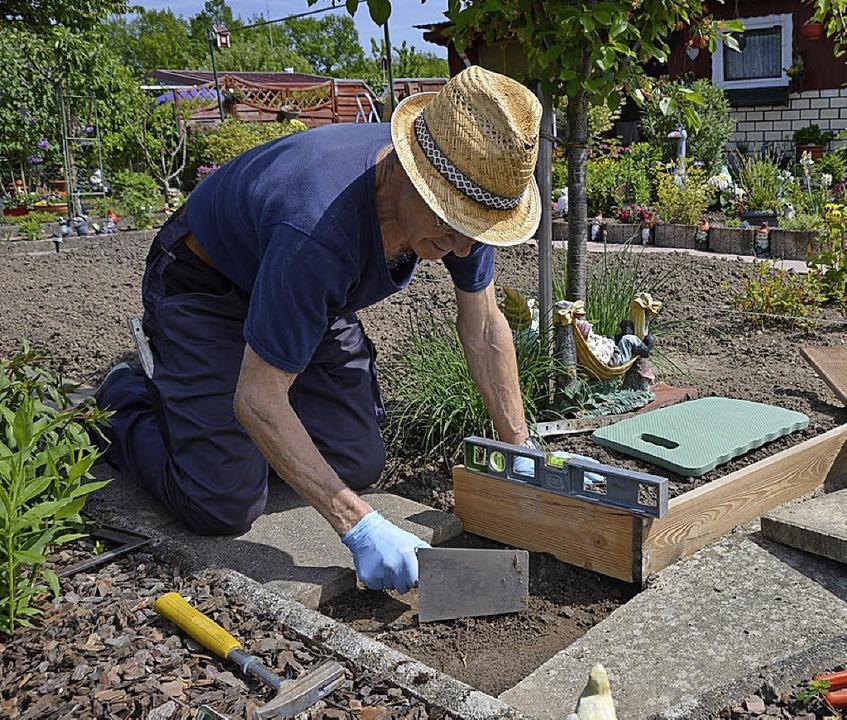 Wolfgang Knoll macht eine neue Einfassung um die Beete in seinem Garten.  | Foto: Horatio Gollin
