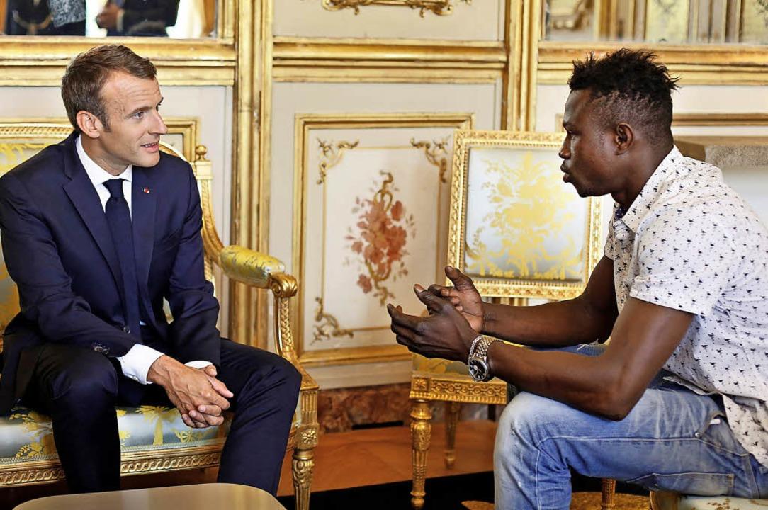 Frankreichs Präsident Emmanuel Macron ...ch bei Lebensretter Mamoudou Gassama.     Foto: AFP