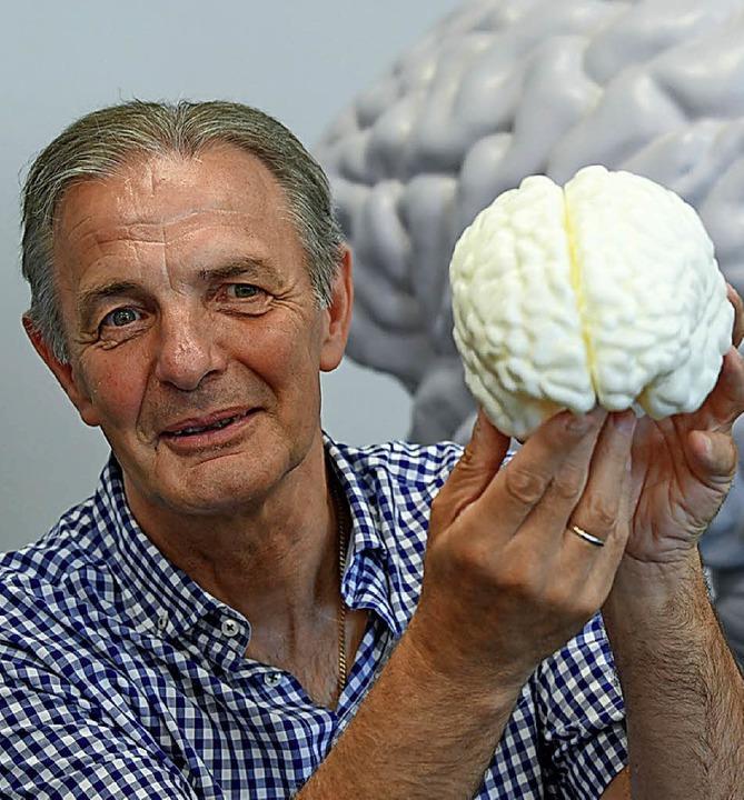 Charly Körber mit einem Modell seines Gehirns   | Foto: dpa
