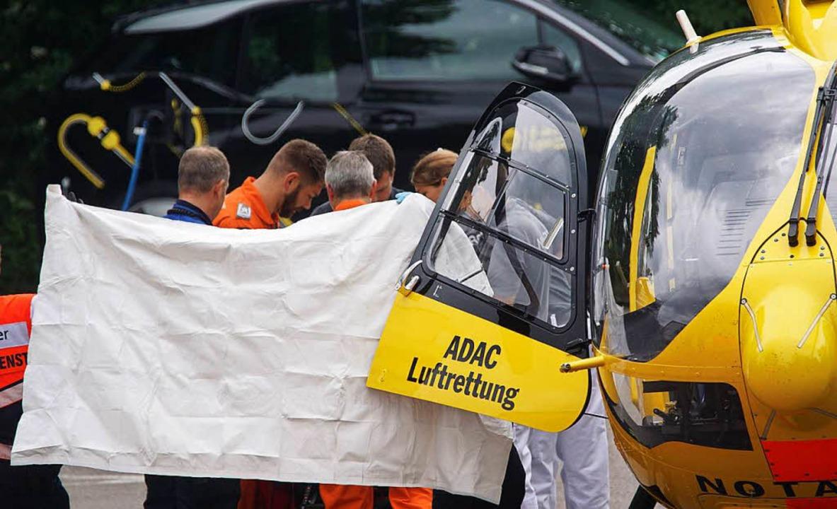 Rettungssanitäter stehen hinter einem ... Er hat schwere Verletzungen erlitten.  | Foto: dpa