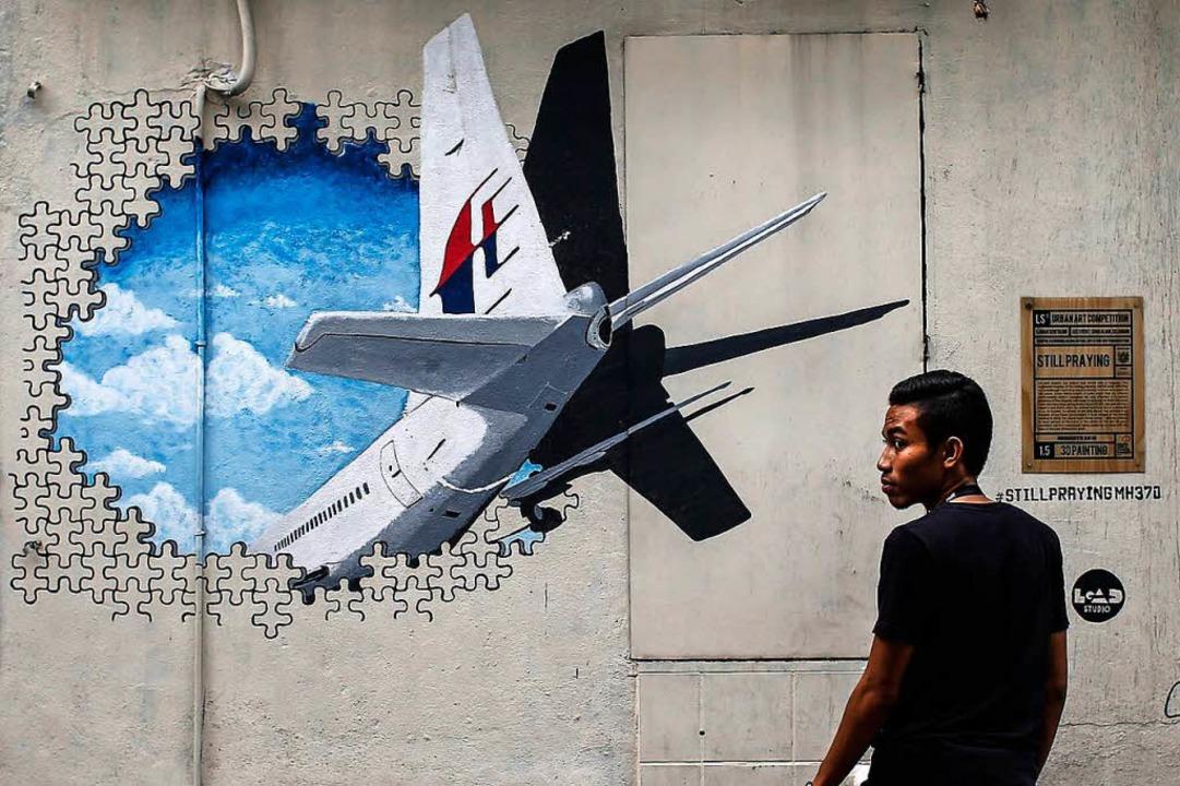 Ein Mann steht vor einem Wandgemälde i...-Airlines-Flugs MH370 dargestellt ist.    Foto: dpa