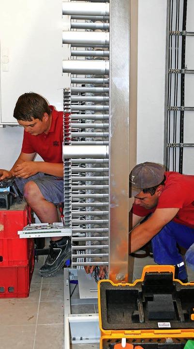 Mitarbeiter der Firma Vetter verlegen ...Verteiler bereits die Glasfaserkabel.   | Foto: Martin Wunderle