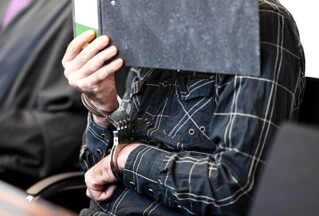 Mit einem Ordner verdeckte W. am Mittw...r Beginn der Verhandlung sein Gesicht.  | Foto: dpa