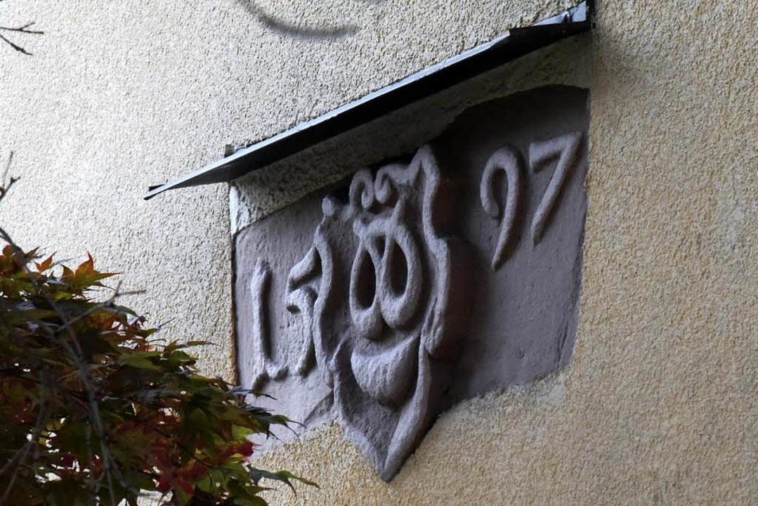 Inschrift, die sich an der Fassade hinter einem dichten Blattervorhang verbirgt  | Foto: Markus Zimmermann