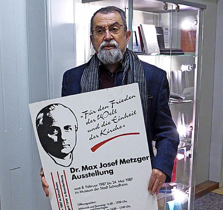 Heiner A. Baur präsentiert ein Ausstellungsplakat zu Max Josef Metzger.   | Foto: Privat