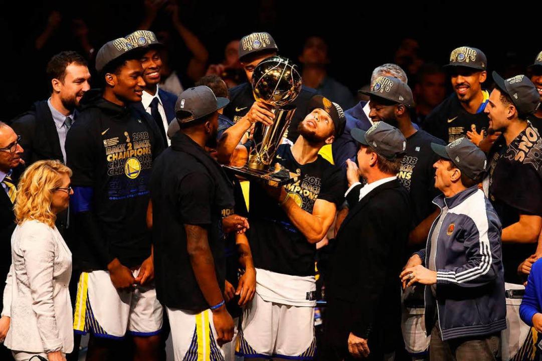 Steve Curry hebt den Pokal hoch.  | Foto: AFP
