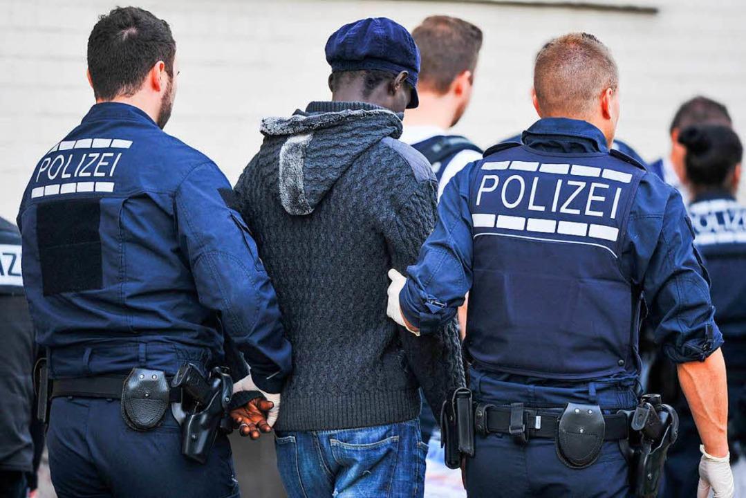 Polizisten führen bei einer Razzia in ...Flüchtlingsheim einen Verdächtigen ab.  | Foto: dpa