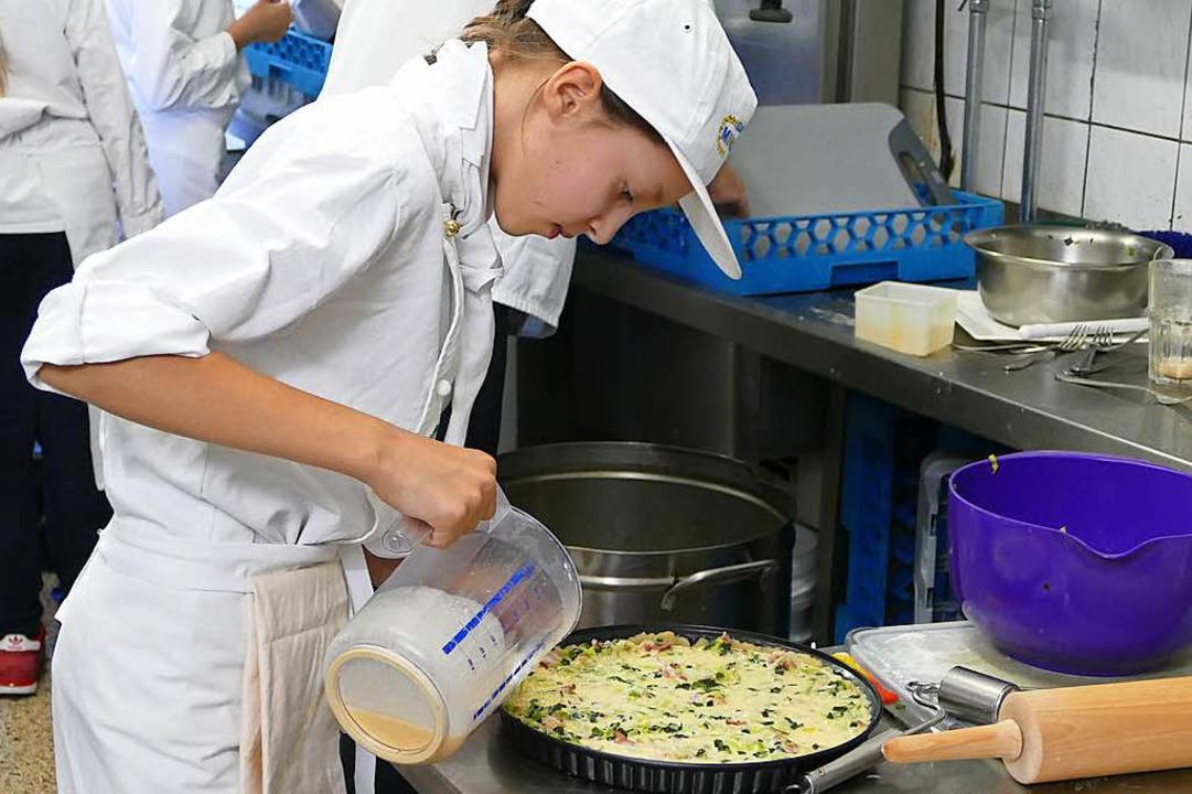 Junge Köche bereiten eine Quiche zu.  | Foto: Lena Roser