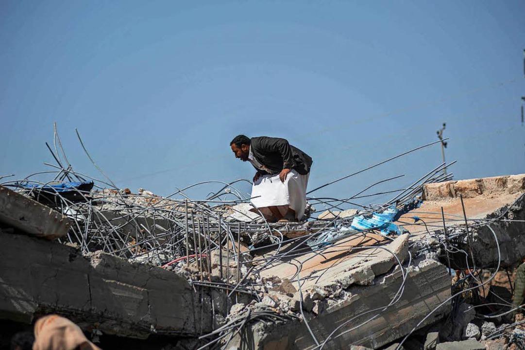 Ein Mann steht in den Trümmern eines G...itärkoalition im Mai getroffen wurde.     Foto: DPA