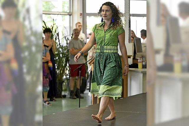 Frauen und Mädchen zeigen Einzelstücke, die Langzeitarbeitslose aus gespendeter Kleidung gefertigt haben