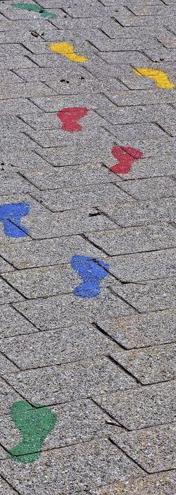 Die bunten Fußspuren weisen auf dem Hof den Weg zum Vier-Elemente-Pfad.  | Foto: Susanne Gilg