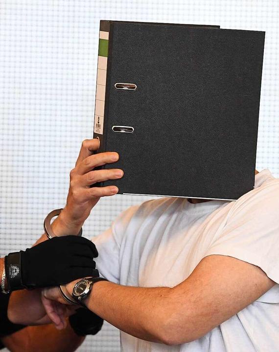 Der 44 Jahre alte Angeklagte in einem ...ht sein Gesicht mit einem Aktenordner.  | Foto: dpa