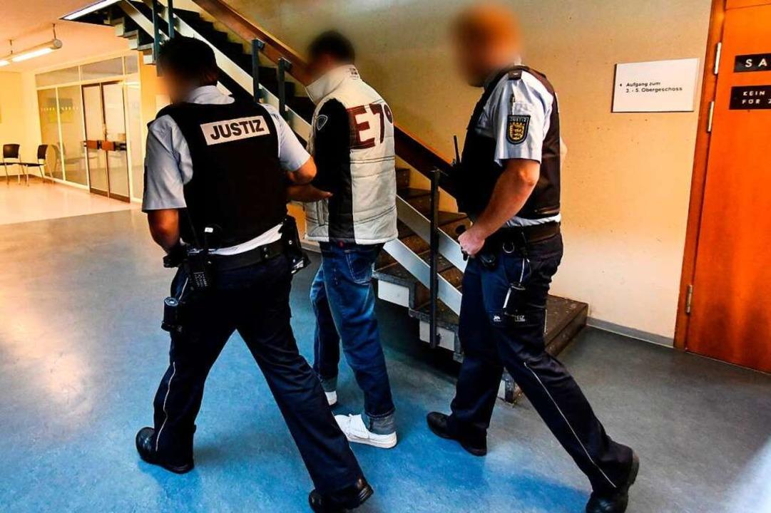 Christian L. wird am ersten Prozesstag von Justizbeamten abgeführt.  | Foto: dpa
