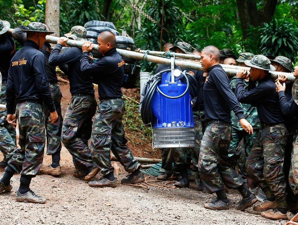 Soldaten tragen eine Pumpe, mit der da...ser aus der Höhle gepumpt werden soll.  | Foto: dpa