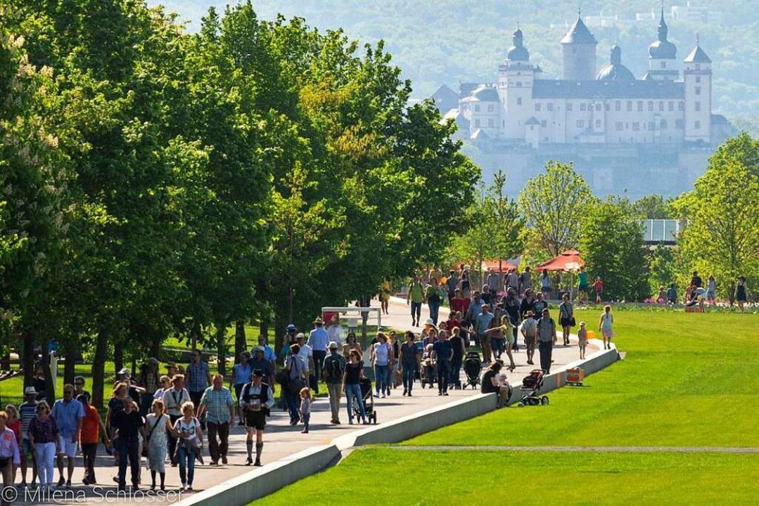 Besucher der Landesgartenschau in Würzburg blicken auf die Festung Marienberg.  | Foto: Milena Schlosser