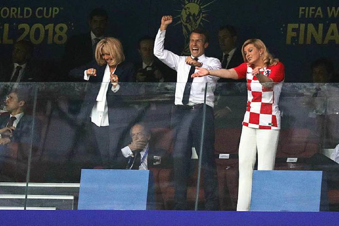 Macron (Mitte) bejubelt ein Tor  neben...echts), Staatspräsidentin von Kroatien  | Foto: dpa
