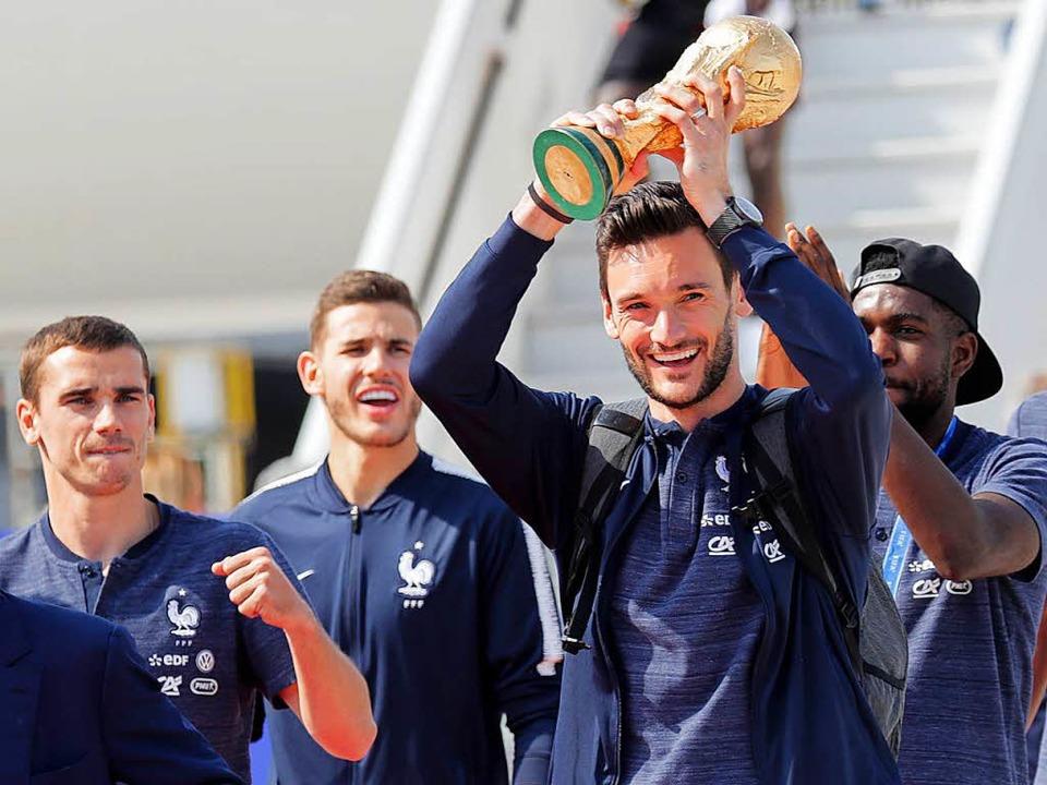 Ankunft in Paris – der Kapitän des Teams zeigt die Trophäe.  | Foto: AFP