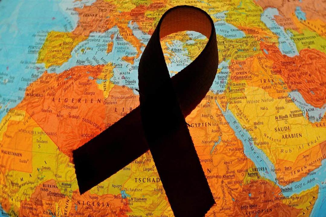 Eine rote Aids-Schleife liegt auf einem Globus     Foto: dpa