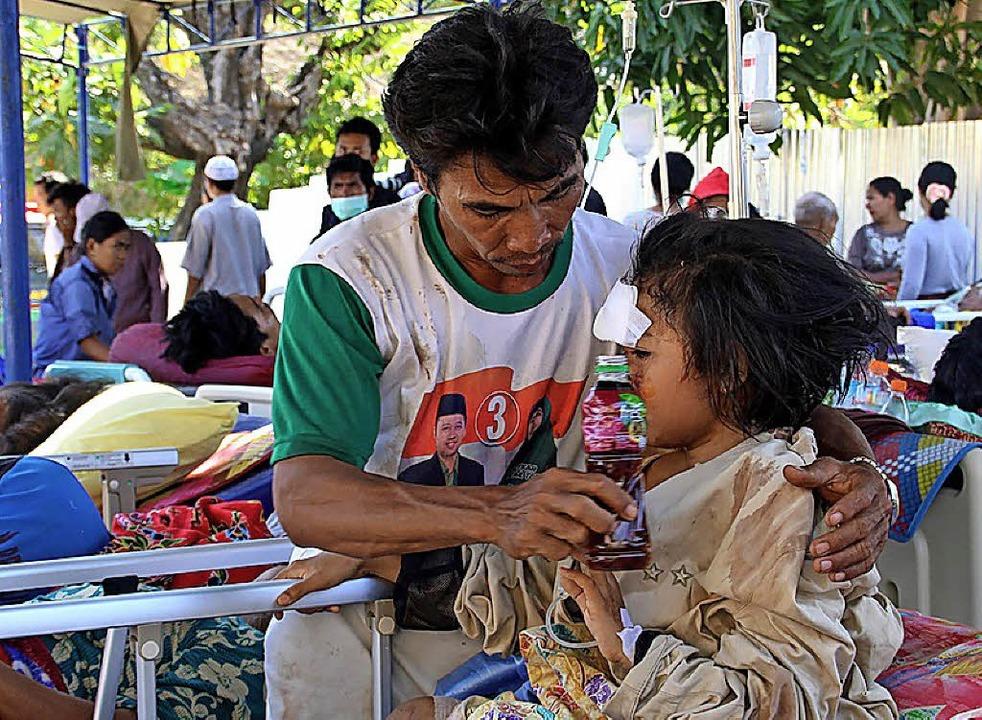 Notdürftig werden die Verletzten auf Lombok von Helfern versorgt.   | Foto: AFP
